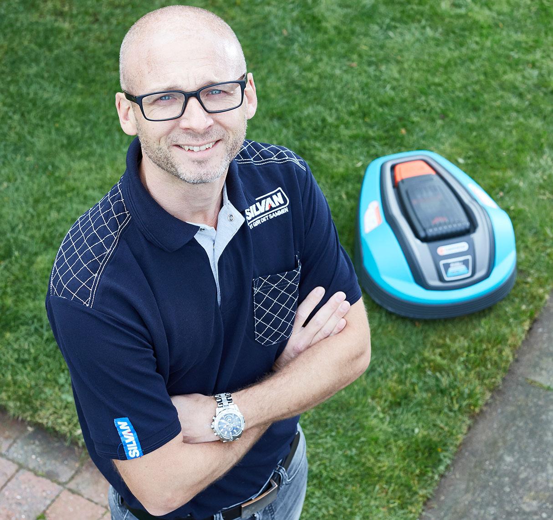 Klaus Jensen, produktchef SILVAN, robotplæneklipperen i baggrunden