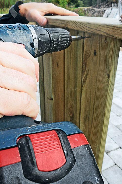 Gelænderet og rækværket skrues på verandaen i gårdspladsen