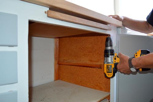 Bor for og skru bordpladen fast i køkkenelementerne.