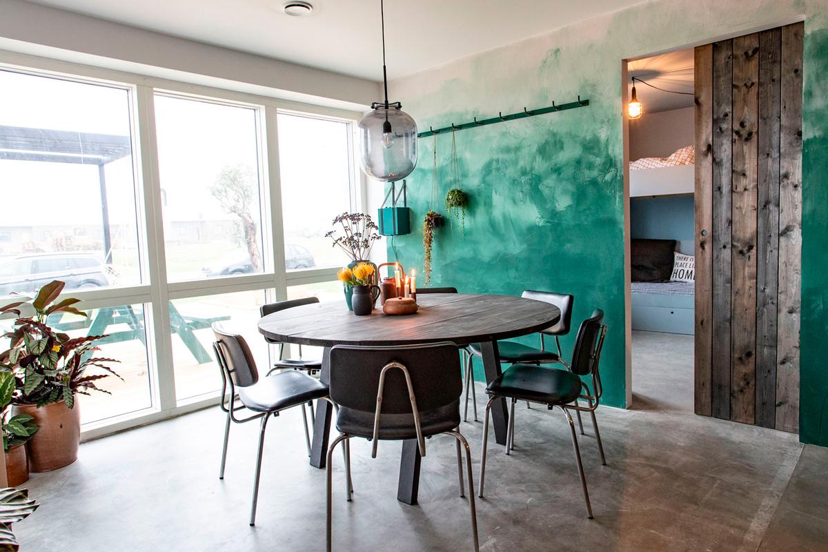 Stuen i grønt hus med Lourdes og Nicolais runde spisebord